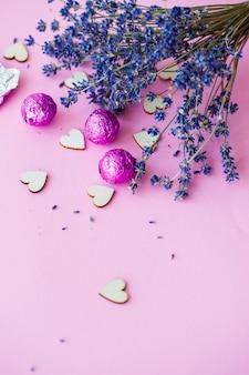 Valentijnsdag achtergrond. rij houten harten op een roze achtergrond, zijaanzicht van een tak van droge lavendel. valentijnsdag concept. bovenaanzicht, plaats voor een inscriptie, reclame. selectieve focus
