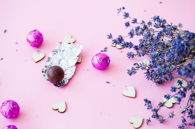 Valentijnsdag achtergrond. rij houten harten op een roze achtergrond, zijaanzicht van een tak van droge lavendel. valentijnsdag concept. bovenaanzicht, plaats voor een inscriptie, reclame