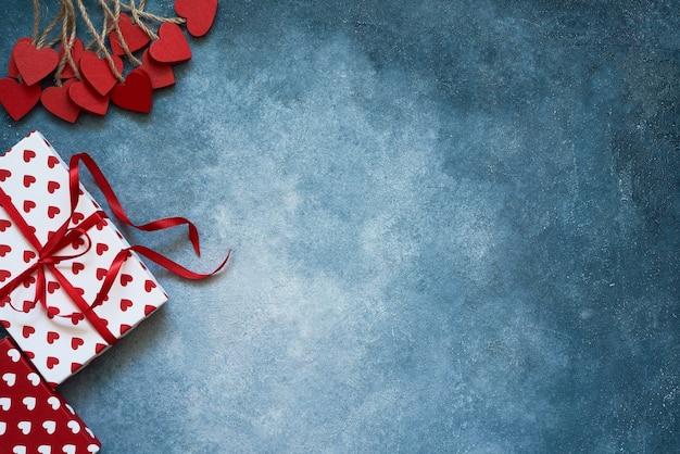 Valentijnsdag achtergrond. rode harten en geschenkdozen op blauwe achtergrond. kopieer ruimte, bovenaanzicht