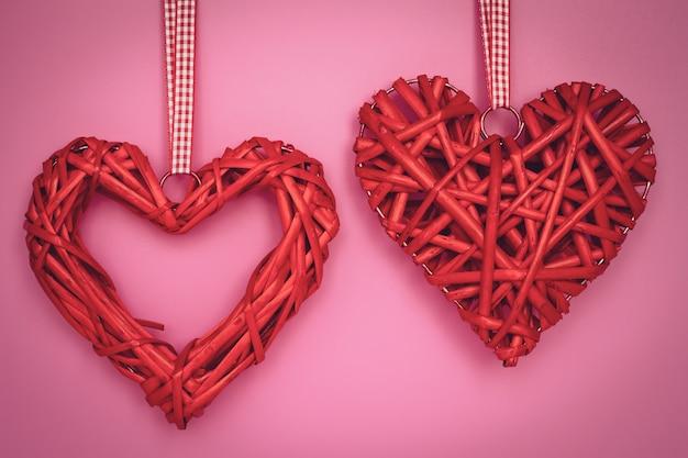 Valentijnsdag achtergrond. romantische wenskaart in vintage stijl. twee handgemaakte harten aan een touw op roze achtergrond.