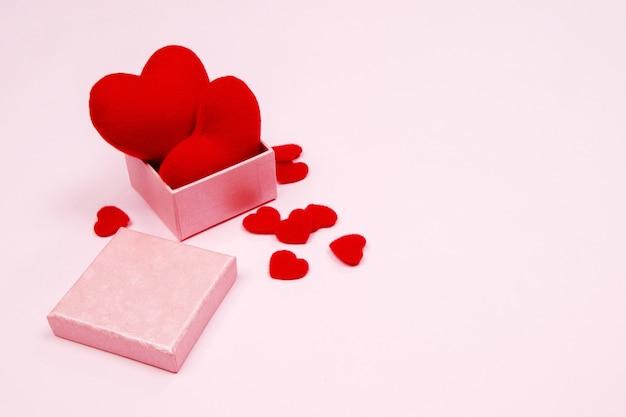 Valentijnsdag achtergrond. rood hart in roze geschenkdoos op roze achtergrond