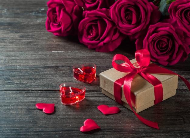 Valentijnsdag achtergrond, rozen en geschenken op een houten bord