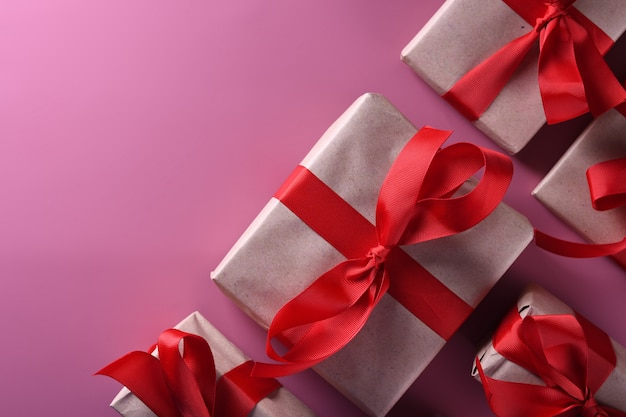 Valentijnsdag achtergrond wenskaart liefdesymbolen, rode decoratie met geschenkdozen op roze achtergrond. bovenaanzicht met kopie ruimte en tekst. plat leggen