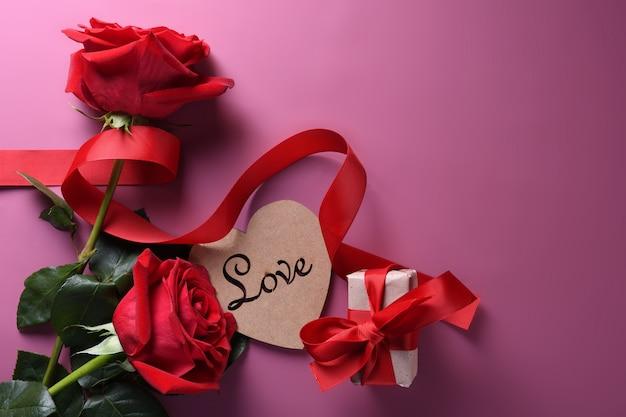 Valentijnsdag achtergrond wenskaart liefdesymbolen, rode decoratie met glazen hart rozen geschenken op roze achtergrond. bovenaanzicht met kopie ruimte en tekst. plat leggen