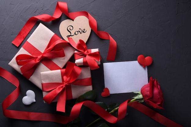 Valentijnsdag achtergrond wenskaart liefdesymbolen, rode decoratie met glazen hart rozen geschenken op stenen achtergrond. bovenaanzicht met kopie ruimte en tekst. plat leggen