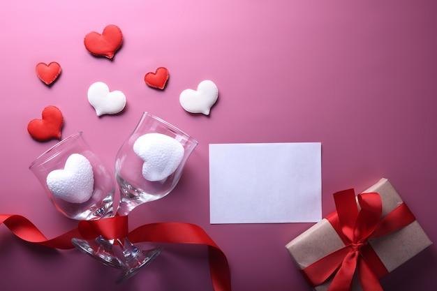 Valentijnsdag achtergrond wenskaart liefdesymbolen, rode decoratie met glazen op roze achtergrond. bovenaanzicht met kopie ruimte en tekst. plat leggen