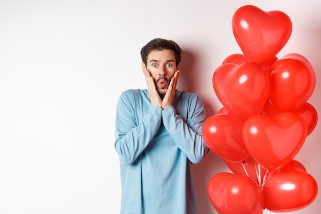Valentijnsdag. afbeelding van een jonge man die in de buurt van hartenballonnen staat met een geschokt gezicht, geschrokken starend naar de camera, witte achtergrond.