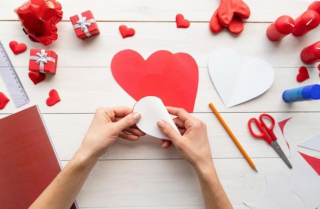 Valentijnsdag ambachtelijke diy. stap voor stap instructie voor het maken van papieren hartvormige luchtballon. stap 4 - vouw elk hart in tweeën Premium Foto