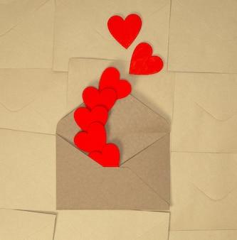Valentijnsdag ambachtelijke envelop met rode harten op bruin gewoon papier achtergrond, romantische liefde ontwerp bovenaanzicht, kopie ruimte schoonheid