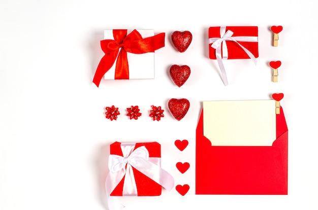 Valentijnsdag attributen met rode romantische harten, kaart, geschenkdozen op witte achtergrond met kopie ruimte