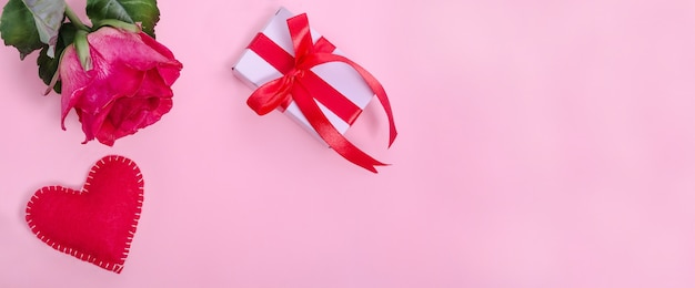 Valentijnsdag banner achtergrond. rode roos met rood hart en een geschenk op een roze achtergrond met kopie ruimte.