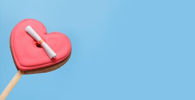 Valentijnsdag banner met geglazuurde koekjes in vorm van hart met liefdesbrief op blauw.