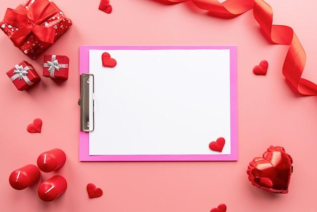 Valentijnsdag. blanco papier op roze klembord met valentijn decoraties kaarsen, ballonnen en confetti