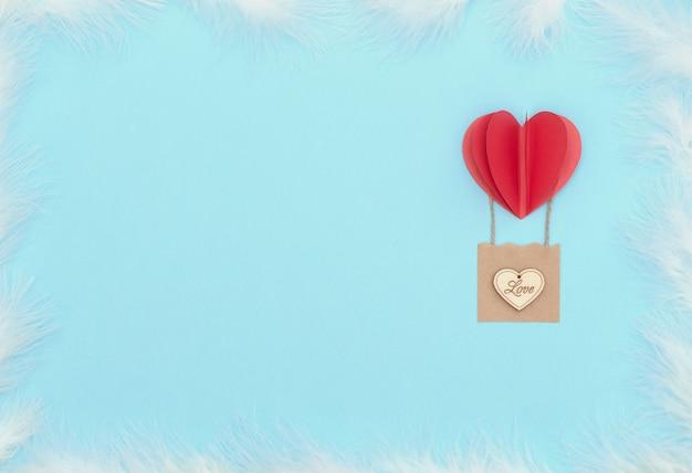 Valentijnsdag blauwe achtergrond met rood hart ballon met mand met houten hart erop en witte veren
