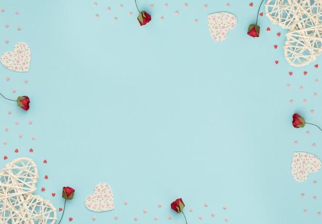 Valentijnsdag blauwe achtergrond met rotan, vilten harten, rode rozen en kleine rode en roze harten