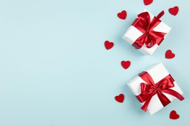 Valentijnsdag, bruiloft of moederdag plat met geschenkdozen met rood lint en hartjes op pastelblauw.