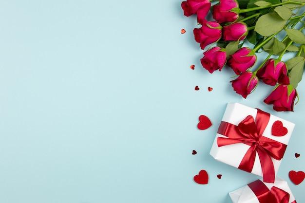 Valentijnsdag, bruiloft of moederdag plat met geschenkdozen met rood lint, rozen en harten op pastelblauw.