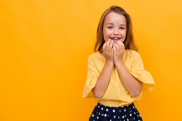Valentijnsdag concept. aantrekkelijk charmant meisje kind in een t-shirt en rok bedekt vreugdevol haar mond met haar hand op een gele achtergrond