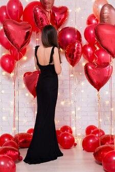 Valentijnsdag concept achteraanzicht van vrouw in zwarte jurk met rode hartvormige ballonnen