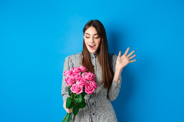Valentijnsdag concept afbeelding van aantrekkelijke jonge vrouw hijgend verbaasd ontvang verrassing bloemen staan...