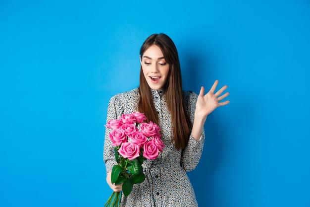 Valentijnsdag concept. afbeelding van een aantrekkelijke jonge vrouw die verbaasd naar adem hapt, verrassingsbloemen ontvangt, staande op een blauwe achtergrond