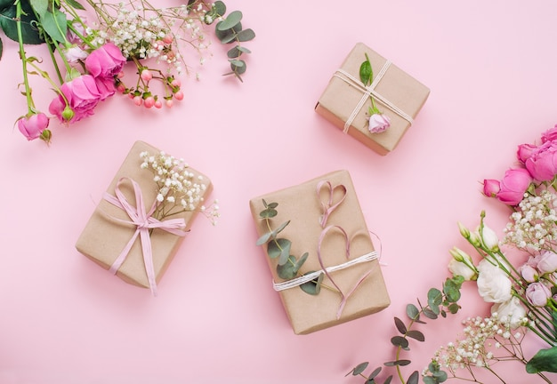 Valentijnsdag concept. ambachtelijke papier geschenkdozen verpakken op roze achtergrond. bovenaanzicht, plat gelegd.