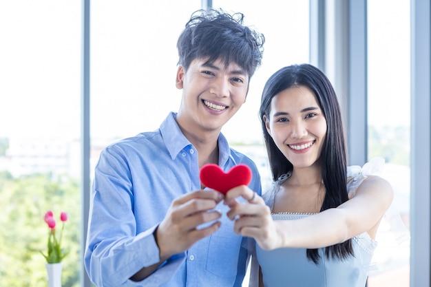 Valentijnsdag concept, aziatische jonge gelukkige zoete paar show verliefd abstracte vervaging met focus show houden klein een rood hartvormig kussen na de lunch op de achtergrond van een restaurant, liefdesverhaal paar