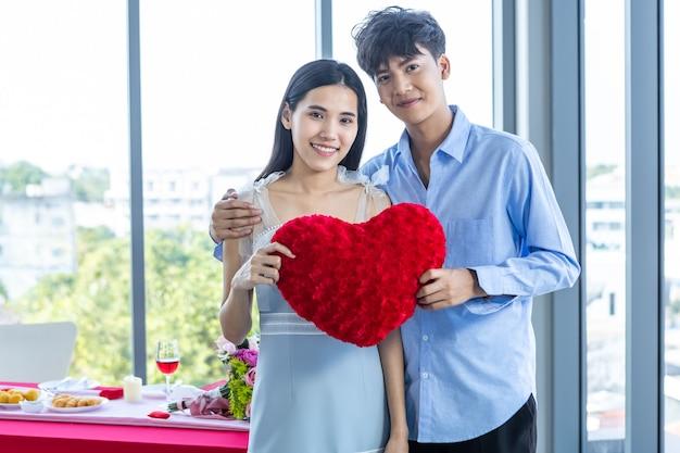 Valentijnsdag concept, aziatische jonge gelukkige zoete paar verliefd met een rood hartvormig kussen na de lunch op de achtergrond van een restaurant, liefdesverhaal paar