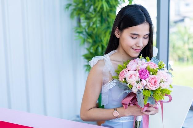 Valentijnsdag concept, blij van lachende aziatische jonge vrouw zittend aan een tafel eten met een boeket rozen op op de achtergrond van het restaurant
