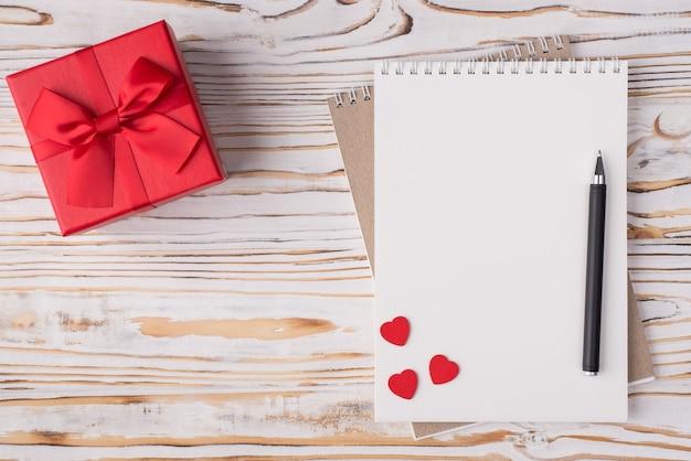 Valentijnsdag concept. boven boven bovenaanzicht plat lag foto van een lege notebook rode huidige rode harten en een pen geïsoleerd op lichte houten achtergrond met copyspace