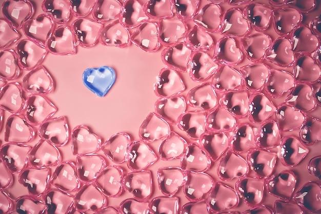 Valentijnsdag concept. een blauw hart in een omgeving glas transparante harten op roze achtergrond, glazen hart gloeit, glas schilderen. veel rode glazen harten. liefde voor valentijnsdag. ruimte kopiëren.