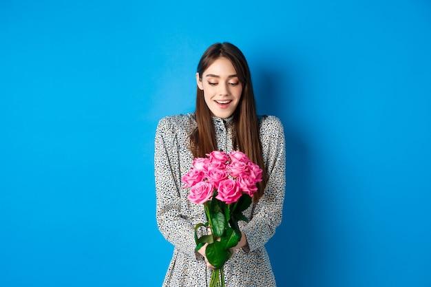 Valentijnsdag concept. gelukkig aantrekkelijke vrouw ontvangt verrassingsbloemen, dankbaar kijkend naar boeket roze rozen, staande op blauwe achtergrond.