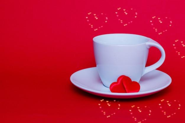 Valentijnsdag concept gemaakt van koffiekopje en rode papieren harten.