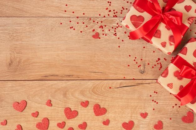 Valentijnsdag concept. geschenkdozen en rode glitter hartjes op houten. plat leggen, ruimte kopiëren
