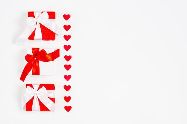 Valentijnsdag concept. geschenkdozen met rode linten en rode glanzende harten.