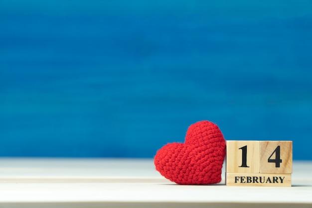 Valentijnsdag concept. hand maken garen rood hart naast houten blok kalender ingesteld op valentines datum 14 februari