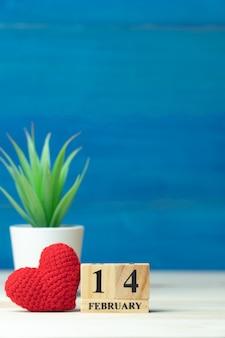 Valentijnsdag concept. hand maken garen rood hart naast houten blok kalender