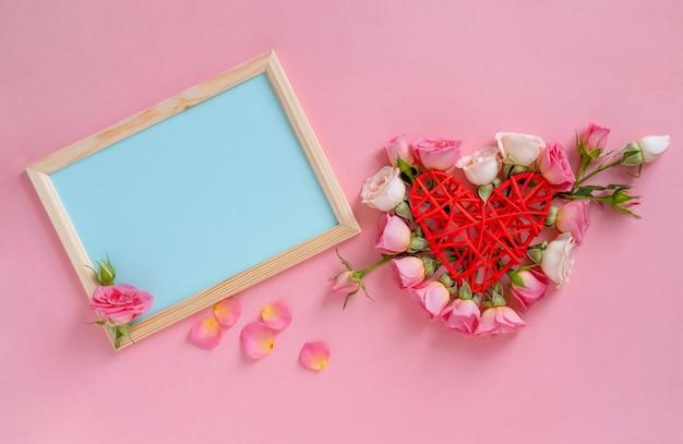 Valentijnsdag concept. hartvorm gemaakt van bloemen. valentijnsdag achtergrond. rozen op pastel roze achtergrond.