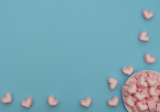 Valentijnsdag concept. hartvormige marshmallows in witte kom op blauwe achtergrond.