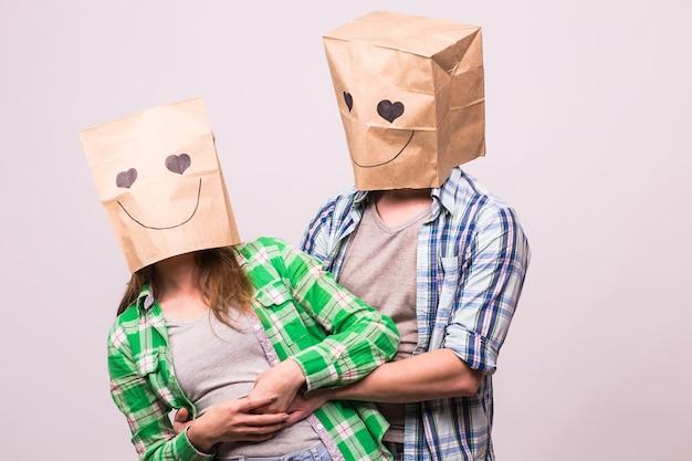 Valentijnsdag concept - jong liefdespaar met zakken over hoofden op witte achtergrond