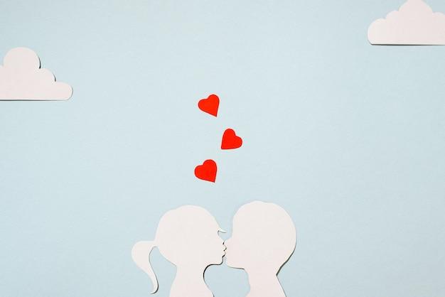 Valentijnsdag concept. kartonnen silhouetten meisje en jongen kussen. creatieve liefdeskaart. rode harten, wolken op een pastel blauwe achtergrond. plat lag, bovenaanzicht.
