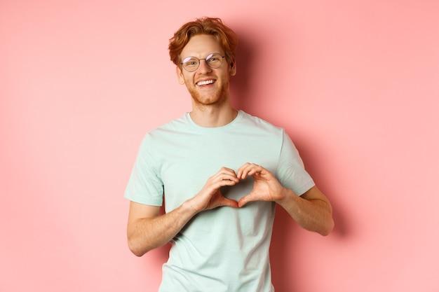 Valentijnsdag concept. knappe roodharige man in glazen, hart teken tonen en zeggen ik hou van jou, staande op roze achtergrond.
