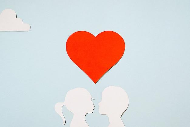Valentijnsdag concept. kussen meisje en jongen silhouetten. creatieve liefdeskaart. rood hart en wolken op een pastel blauwe achtergrond. plat lag, bovenaanzicht.