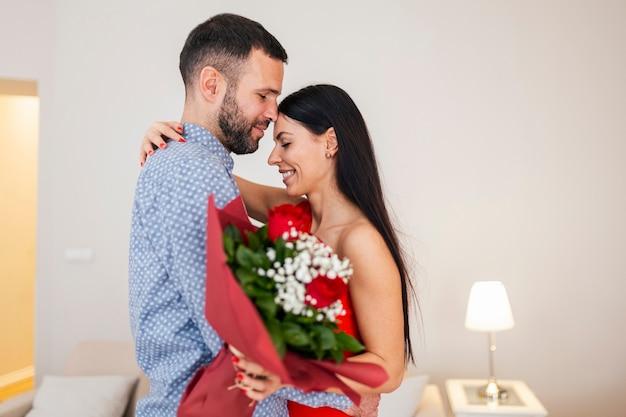 Valentijnsdag concept. liefhebbers die elkaar knuffelen. knappe man verrast zijn vriendin met rode rozen thuis