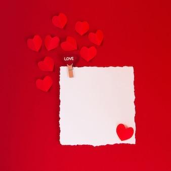 Valentijnsdag concept met rode harten op rode achtergrond en witte kaart voor tekst, plat leggen, kopieer ruimte