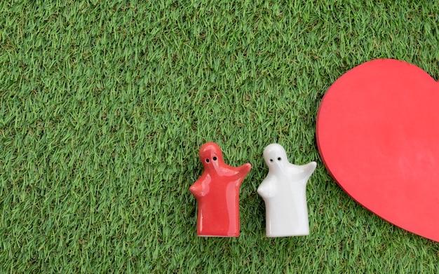 Valentijnsdag concept mock-up paar knuffelen op grasvloer en half hart met kopieerruimte