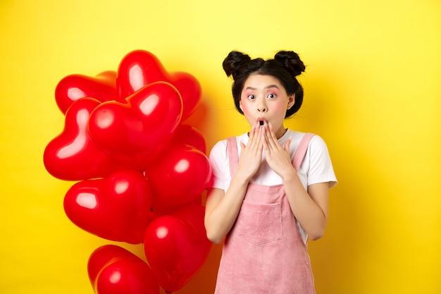 Valentijnsdag concept. onder de indruk koreaans meisje zegt wauw, hijgend en hand in hand bij geopende mond