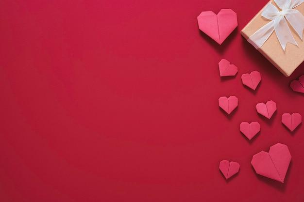 Valentijnsdag concept, rood hart met gele geschenkdoos op rode achtergrond.