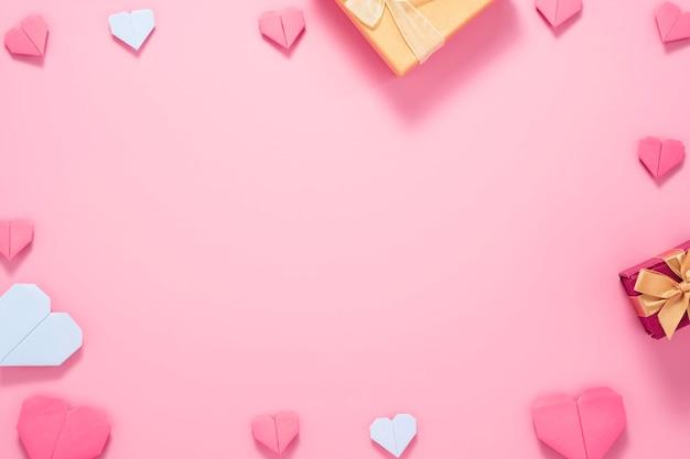 Valentijnsdag concept, rood hart met gele geschenkdoos op roze achtergrond.
