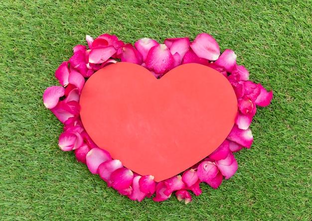 Valentijnsdag concept roze rozenblaadjes gerangschikt in hartvorm met rood hart